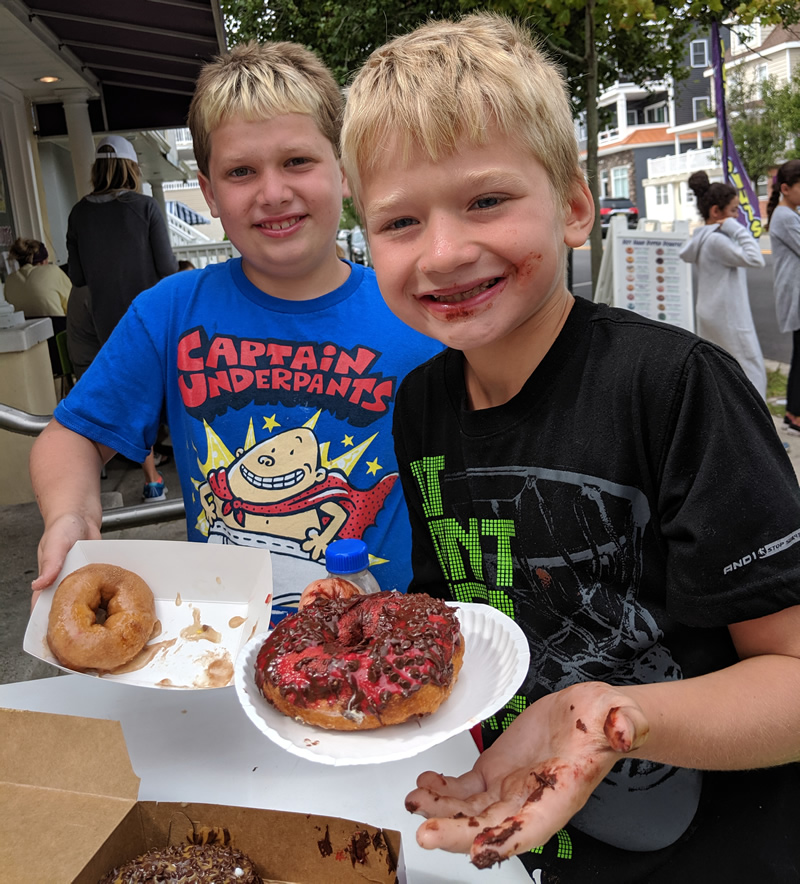 Children with messy hands eating chocolate donuts